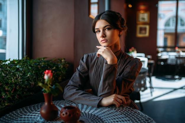 Ritratto di giovane e bella signora retrò nella caffetteria