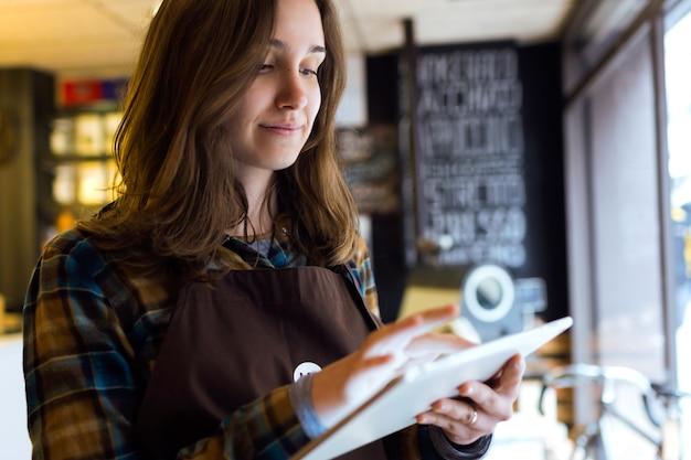 Ritratto di giovane e bella commessa che utilizza la sua tavoletta digitale in un negozio biologico.