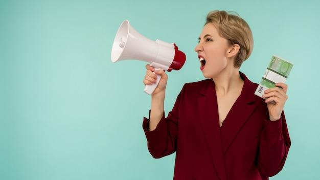 Ritratto di giovane e bella imprenditrice urlando con soldi e megafono, su sfondo blu - immagine
