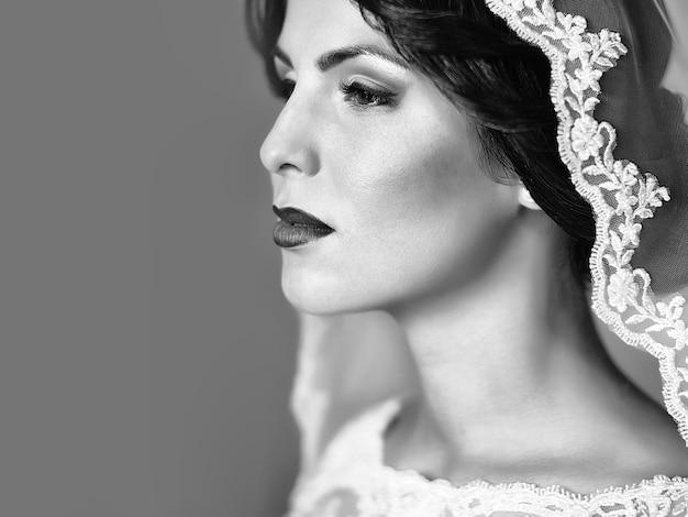 Ritratto di bella giovane sposa sensuale in abito di pizzo bianco e velo sulla testa che guarda lontano.