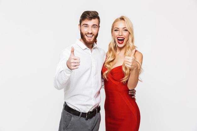 Ritratto di una bella giovane coppia vestita intelligente in piedi isolato su bianco, che celebra il nuovo anno, dando i pollici in su