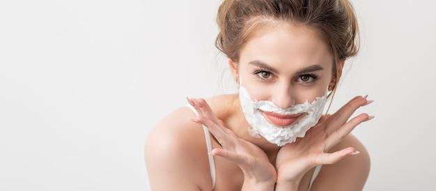 Ritratto di una giovane e bella donna caucasica sorridente con schiuma da barba sul viso posa su sfondo bianco...