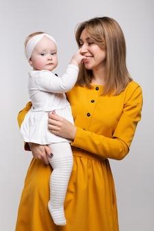Ritratto di una bellissima giovane madre sorridente con un bambino in braccio