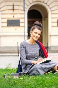 Ritratto di una bella giovane studentessa sorridente che studia con un libro sull'erba vicino al palazzo dell'università