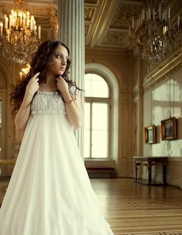 Ritratto di una giovane e bella signora vittoriana in abito bianco. palazzo russo.