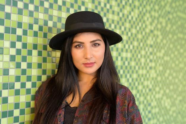 Ritratto di giovane e bella donna contro il muro colorato