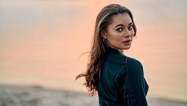 Ritratto di giovane e bella donna in abito nero sulla spiaggia. giovane modello femminile caucasico in riva al mare.