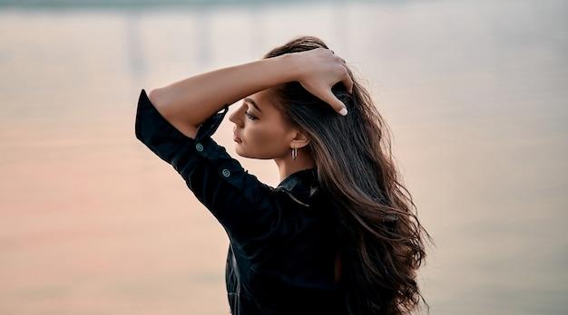 Ritratto di bella giovane donna in abito nero raddrizza i capelli ricci lunghi sulla spiaggia. giovane modello femminile caucasico in riva al mare.