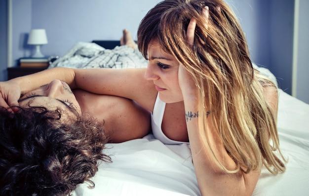 Ritratto di giovane e bella donna che accarezza il viso dell'uomo sdraiato su un letto. amore e concetto di relazioni di coppia.