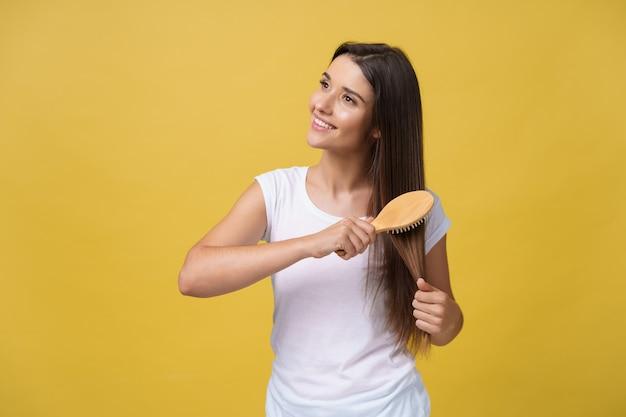 Ritratto di giovane e bella donna che si pettina i capelli, che guarda l'obbiettivo e sorridente.