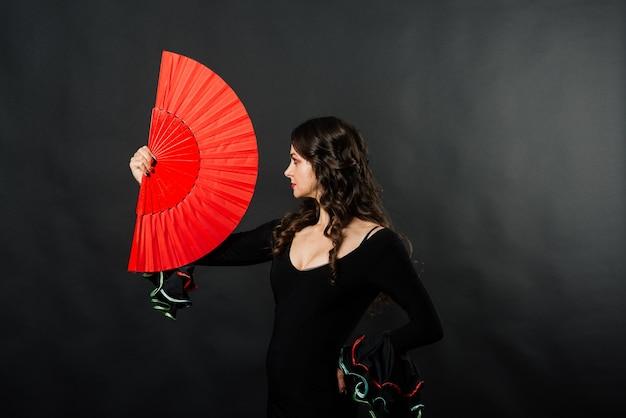 Ritratto di giovane e bella donna che balla flamenco con ventilatore in studio