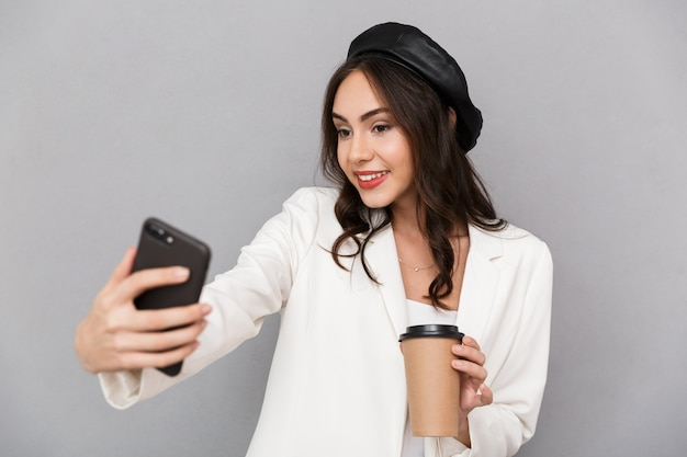 Ritratto di una giovane e bella donna vestita in giacca su sfondo grigio, tenendo la tazza di caffè, prendendo un selfie con il telefono cellulare