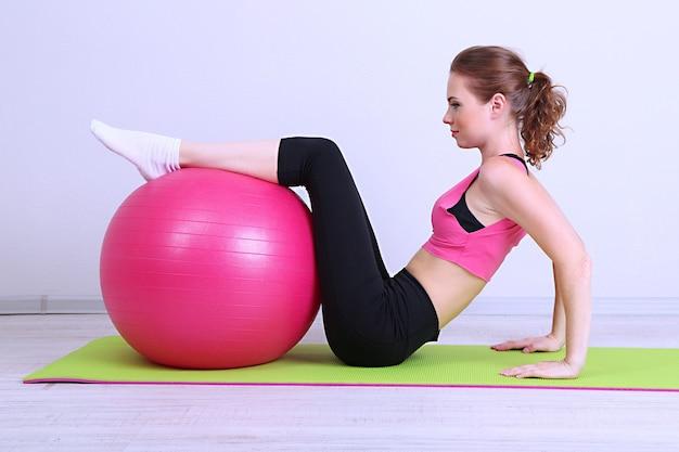 Ritratto di bella giovane donna si esercita con la palla da ginnastica