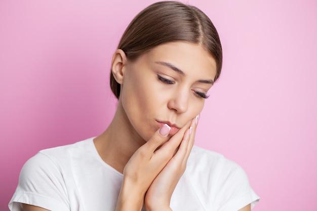 Ritratto di una giovane e bella donna che sperimenta un doloroso mal di denti.