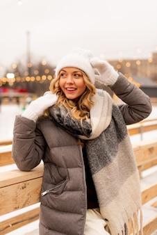 Ritratto di bella giovane donna sul rango di ghiaccio di natale festivo. signora che indossa vestiti a maglia caldi invernali.