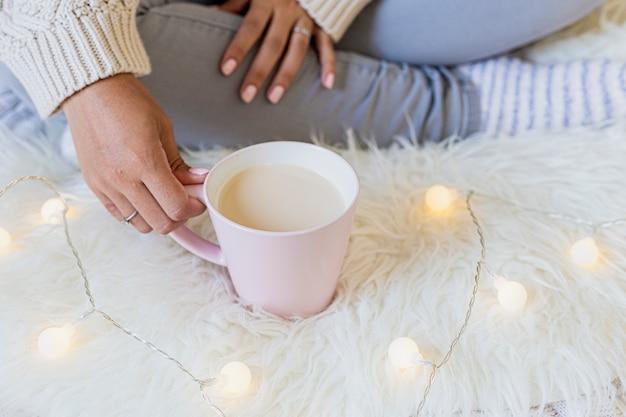 Ritratto di una bellissima giovane donna in possesso di una tazza di caffè caldo
