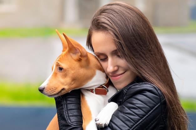 Ritratto di giovane e bella donna che abbraccia il suo cane purosangue basenji congo terrier