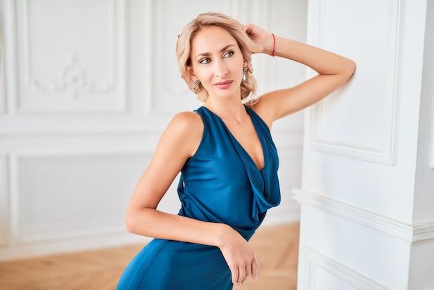 Ritratto di una giovane e bella donna in un lussuoso abito blu in posa in uno studio