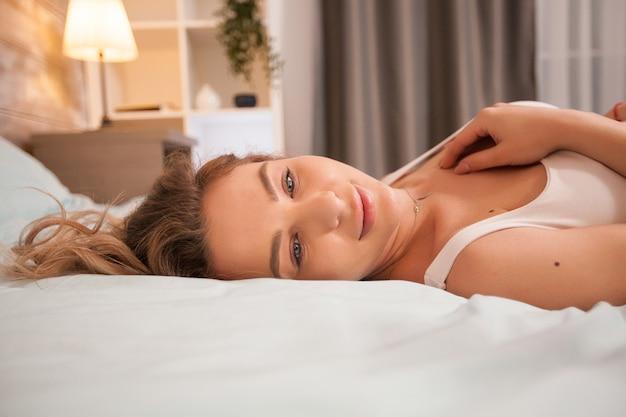 Ritratto di giovane e bella donna in pigiama di notte che riposa a letto.