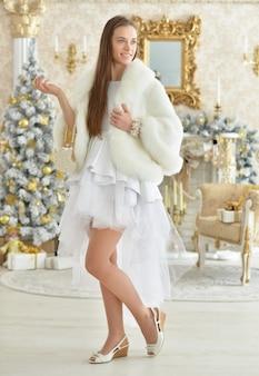 Ritratto di bella giovane donna in posa in una stanza decorata per le vacanze di natale