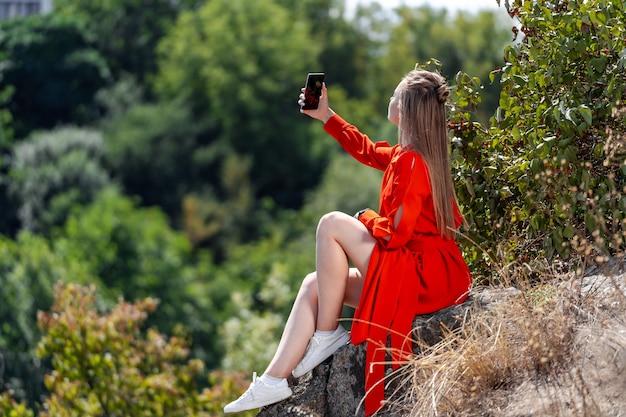 Ritratto di una bellissima giovane donna in abito lungo rosso