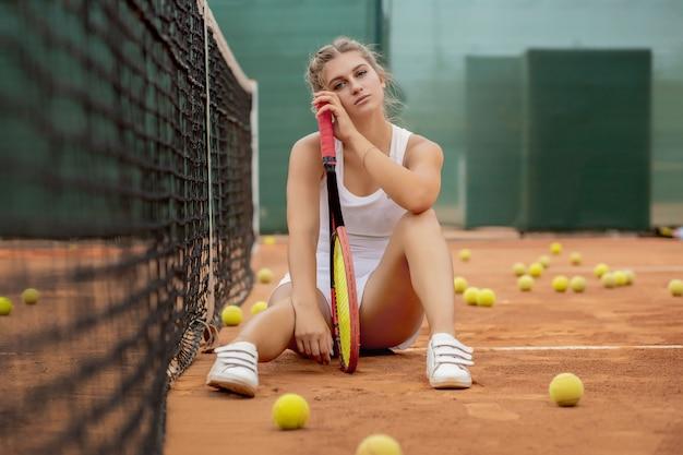 Ritratto di giovane e bella donna seduta vicino a rete nel campo da tennis con palla all'aperto