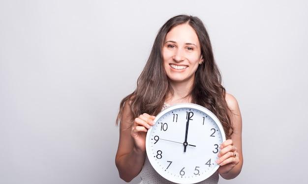 Ritratto di giovane e bella donna sorridente e tenendo grande orologio bianco a dodici un orologio