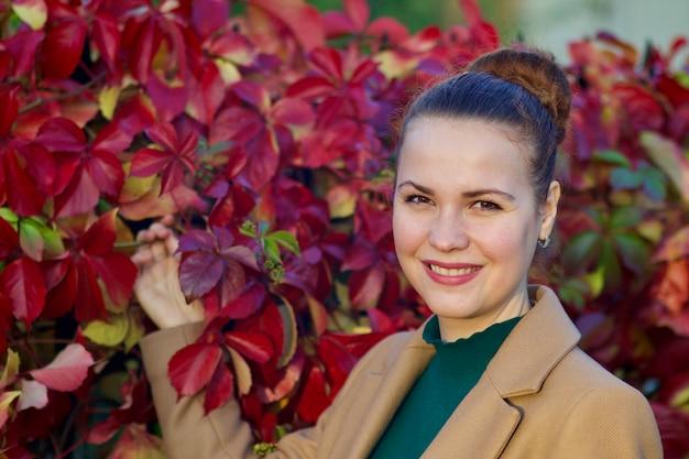 Ritratto di giovane e bella donna in piedi vicino a cespuglio di foglie di vite selvatiche autunno rosso e sorridente.