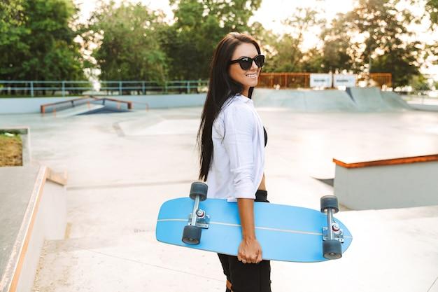 Ritratto di giovane e bella donna in streetwear sorridente mentre trasporta skateboard in park
