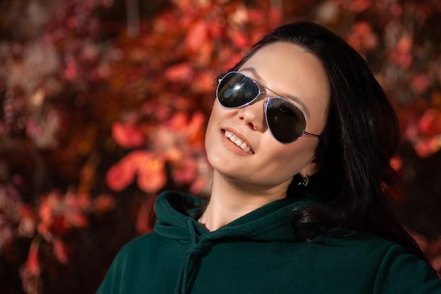 Ritratto di una giovane e bella donna in occhiali da sole nella foresta di autunno al tramonto.