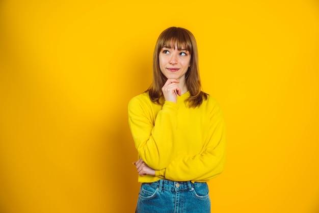 Ritratto di giovane e bella donna che pensa in posa in abbigliamento casual comodo isolato su sfondo giallo brillante