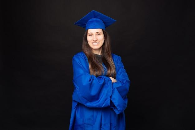 Ritratto di giovane e bella donna che indossa scapolo e cappello di laurea e in piedi sulle braccia incrociate