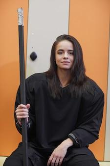 Ritratto di giovane e bella donna che indossa attrezzi da hockey