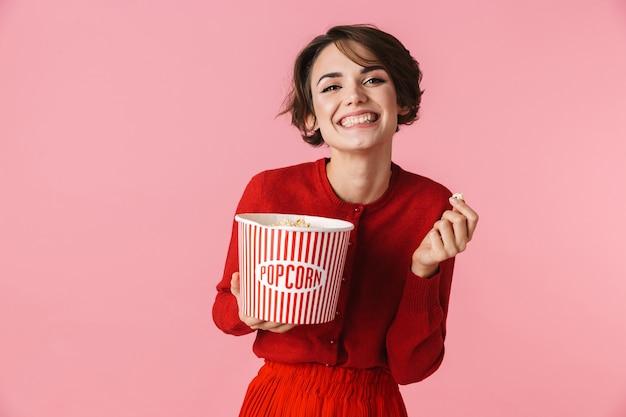 Ritratto di una giovane e bella donna che indossa un abito rosso in piedi isolato su sfondo rosa, mangiando popcorn