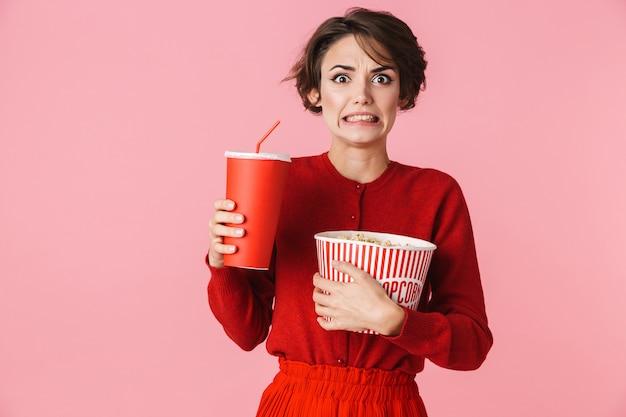 Ritratto di una giovane e bella donna che indossa un abito rosso in piedi isolato su sfondo rosa, tenendo il bicchiere di plastica con drink, mangiando popcorn