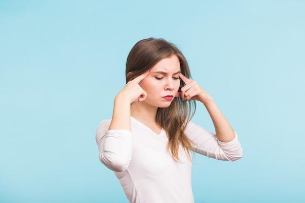 Ritratto di bella giovane donna con le spalle nude che tocca le sue tempie sensazione di stress, sull'azzurro