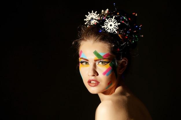 Ritratto di giovane e bella donna con trucco creativo su sfondo nero
