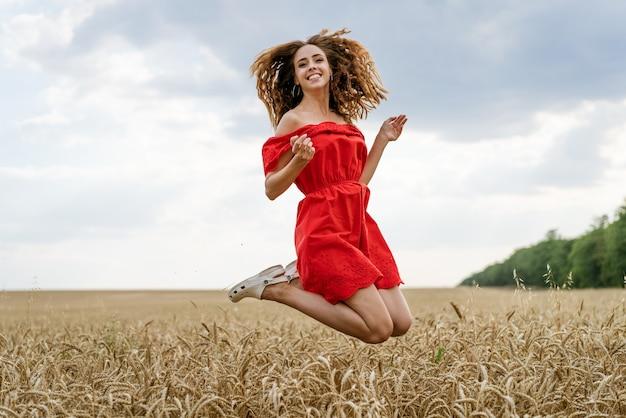 Ritratto di bella giovane donna con capelli ricci in un vestito rosso in un campo di grano