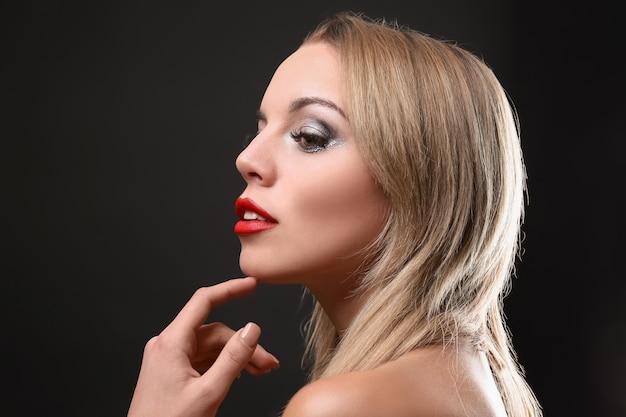 Ritratto di bella giovane donna con le estensioni delle ciglia sul nero