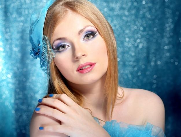 Ritratto di bella giovane donna con trucco glamour, sulla superficie blu