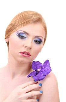 Ritratto di bella giovane donna con trucco glamour e fiore, isolato su bianco
