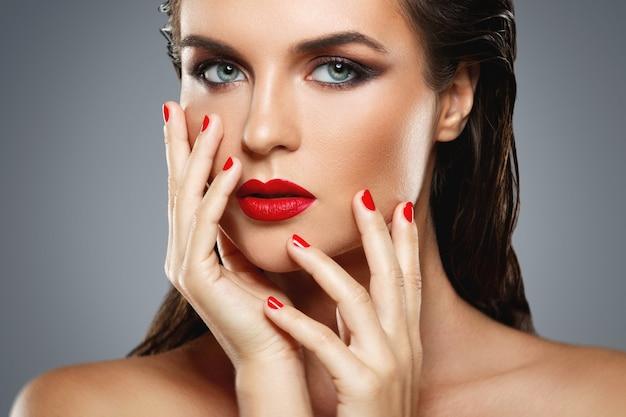 Ritratto di giovane e bella donna con un rossetto rosso e smalto