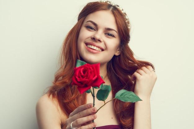 Ritratto di una bellissima giovane donna con una rosa, sorriso