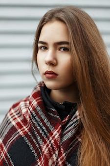 Ritratto di una giovane e bella donna con una sciarpa sullo sfondo della parete in legno