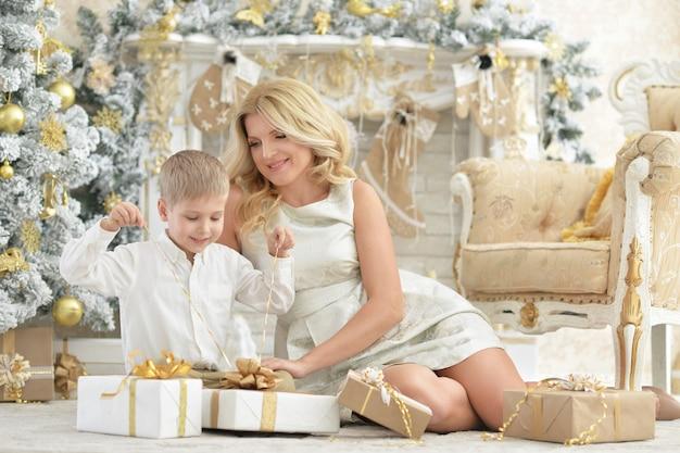 Ritratto di bella giovane donna con figlio in posa in una stanza decorata per le vacanze di natale