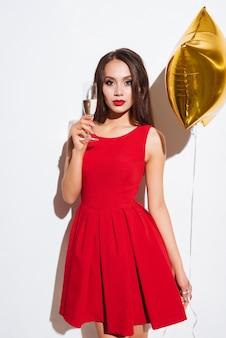 Ritratto di giovane e bella donna con palloncino a forma di stella che beve champagne su sfondo bianco