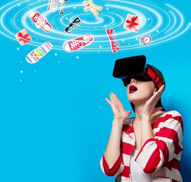 Ritratto di giovane e bella donna con gadget di realtà virtuale sullo spazio blu