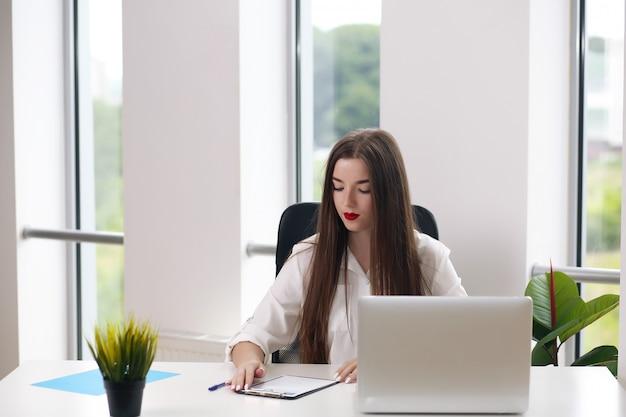 Ritratto di bella giovane donna che lavora con il computer portatile nel suo ufficio.