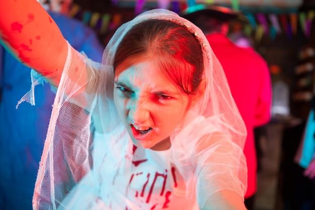 Ritratto di una bellissima sposa zombie che sembra inquietante nella telecamera per halloween. ragazza in abito da diserbo al carnevale di halloween.