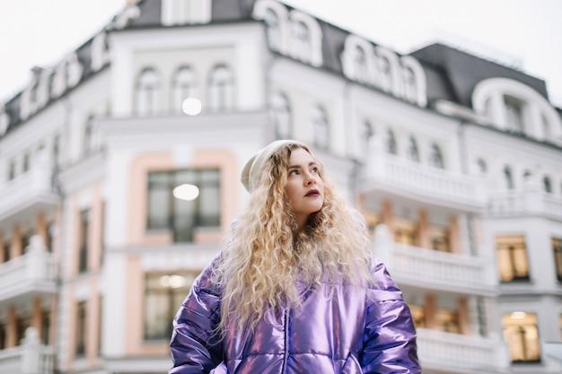 Ritratto di giovane donna caucasica del blondie di modo di bellezza in cappello e cappotto all'aperto. bellezza, concetto di moda